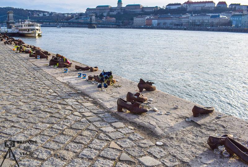 Monumento de los zapatos con el puente de las cadenas y el castillo de Buda de fondo